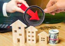 Het concept dalende onroerende goederenmarkt Verminderde rente in de hypotheek Een daling in bezitsprijzen en flats laag stock fotografie