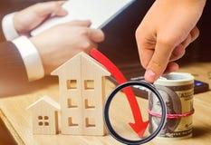 Het concept dalende onroerende goederenmarkt Verminderde rente in de hypotheek Een daling in bezitsprijzen en flats laag royalty-vrije stock fotografie