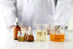 Het concept, de Artsen en de geneeskunde van het schoonheidsproduct experimenten, Apotheker die het chemische product voor schoon Royalty-vrije Stock Afbeeldingen