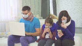 Het concept de epidemie, de familie is ziek en het hoesten, thuis zittend, in medische maskers stock afbeelding