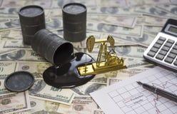 Het concept de oliezaken De vaten olie zijn een bankbiljet van het dollargeld, een gouden boorpomp, een calculator waard stock fotografie