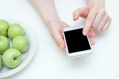 Het concept dieet Een smartphone in de handen van een Kaukasisch meisje en een plaat van appelen op de lijst stock fotografie