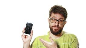Het concept een gebroken gadget De gebaarde gefrustreerde mens toont smartphone met het gebroken scherm stock video