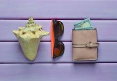 Het concept een toevlucht van het de zomerstrand Portefeuille, shell, hipster zonnebril op een violette houten achtergrond Hoogst Stock Fotografie