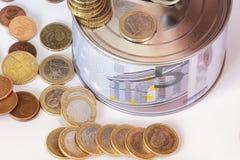 Het concept geld Een spaarvarken in de vorm van een tinblik en, naast het spaarvarken, de geldrekeningen en de muntstukken worden