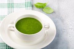 Het concept gezond, vegetarisch of een dieetvoeding: de soep van de roomspinazie, met pijnboomnoten en basilicum Met plakken van  stock foto's
