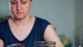 Het concept het gezonde eten Het close-up van een vrouw zet een lepel van fruit en bessenpuree in een mixer stock video