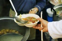 Het concept hoop: Hand-voedt aan behoeftig in de maatschappij: Concept het Voeden: De vrijwilligers geven voedsel aan de armen: h stock afbeelding