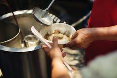 Het concept hoop: Hand-voedt aan behoeftig in de maatschappij: Concept het Voeden: De vrijwilligers geven voedsel aan de armen: h royalty-vrije stock afbeeldingen