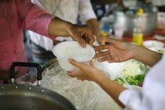 Het concept hoop: Hand-voedt aan behoeftig in de maatschappij: Concept het Voeden: De vrijwilligers geven voedsel aan de armen: h royalty-vrije stock fotografie