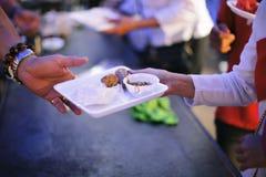 Het concept hoop: Hand-voedt aan behoeftig in de maatschappij: Concept het Voeden: De vrijwilligers geven voedsel aan de armen: h royalty-vrije stock foto