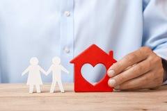 Het concept het huren van een huis, een krediet of een verzekering De mens in overhemd houdt huis en de familie bevindt zich daar stock fotografie