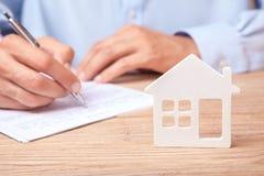 Het concept het huren van een huis, een krediet of een verzekering De mens in overhemd ondertekent contract tegen de achtergrond  stock afbeeldingen