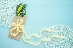 Het concept Internationale de mimosabrunch van de vrouwen` s dag in Kraftpapier-envelopzak op blauwe achtergrond, gele zijdeboog, stock fotografie