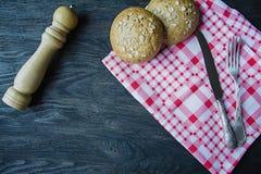 Het concept het koken Vork, voedselmes, geruit servet, broodjes met zonnebloemzaden, houten peperschudbeker bestek stock afbeeldingen