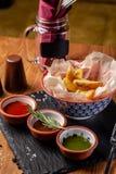 Het concept Mexicaanse keuken Gebakken kruidige aardappels met peper, met verschillende sausen, salsa, guacamole, Spaanse pepers  royalty-vrije stock afbeeldingen