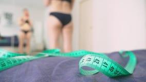 Het concept overgewicht en gewichtsverlies Een vrouw bekijkt zich in de spiegel en fotografeert haar cijfer om te vergelijken stock video