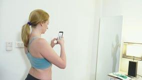 Het concept overgewicht en gewichtsverlies Een vrouw bekijkt zich in de spiegel en fotografeert haar cijfer om te vergelijken stock footage