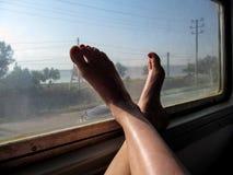 Het concept reis met gemak - vrouwelijke voeten in het treinvenster royalty-vrije stock afbeelding