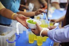 Het concept sociale ongelijkheid: Het schenken van voedsel aan bedelaars om honger te verminderen: De handen van de armen ontvang stock foto's