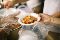 Het concept sociale ongelijkheid: Het schenken van voedsel aan bedelaars om honger te verminderen: De handen van de armen ontvang royalty-vrije stock afbeeldingen