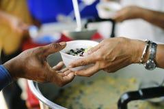Het concept sociale ongelijkheid: Het schenken van voedsel aan bedelaars om honger te verminderen: De handen van de armen ontvang stock afbeeldingen