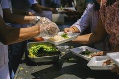 Het concept sociale ongelijkheid: Het schenken van voedsel aan bedelaars om honger te verminderen: De handen van de armen ontvang royalty-vrije stock afbeelding