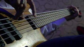 Het concept toont en Vermaak sluit omhoog de hand van de lichaamsdeelmens spelend Bass Guitar-rotsoverleg Prestatiesart. stock video