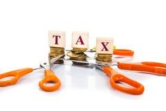 Het concept van besnoeiingsbelastingen met muntstukken en schaar stock afbeelding