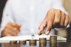 Het concept van het besparingsgeld door Mannelijke hand vooraf in die wordt gesteld die de stapel groeiende zaken zetten die van  royalty-vrije stock foto