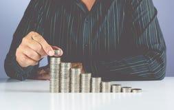 Het concept van het besparingsgeld en hand van zakenman die geldmuntstuk zetten royalty-vrije stock foto