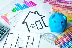 Het concept van het besparingsgeld om in huishuis te investeren De bank van Peggy, calculator en kleurengrafiek op het bureau stock afbeelding