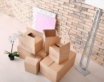 Het concept van het bewegingshuis Kartondozen op vloer stock afbeeldingen