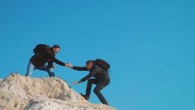 Het concept van het van de bedrijfs groepswerkhulp reissilhouet De groep toeristen leent een helpende hand de klippenbergen bekli stock video