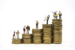 Het concept van de begroting Miniatuurfamilie op muntstukkenstapel Stock Foto