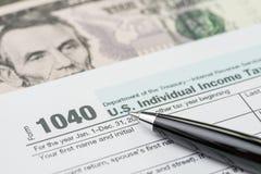Het concept van de belastingstijd, pen die op de individuele inkomstenbelasting van de 1040 V.S.F vullen Royalty-vrije Stock Afbeeldingen
