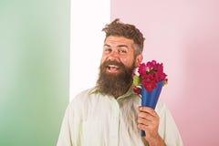Het concept van de bloemenlevering De mens met baard vrolijk gezicht houdt boeket verse bloemen Hipster met baard klaar vakantie royalty-vrije stock afbeelding