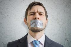 Het concept van de censuur De jonge mens wordt tot zwijgen gebracht met buisband over zijn mond royalty-vrije stock foto's