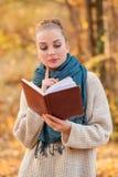 Het concept van de dalingsontspanning met het mooie boek van de vrouwenlezing Stock Foto
