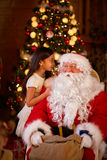 Het concept van de de wintervakantie - meisje het vertellen wens Santa Claus royalty-vrije stock fotografie