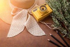 Het concept van de de zomerreis met gele stuk speelgoed camera met de zemelen van de vrouwenhoed Stock Fotografie