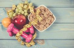 Het concept van de dieetgeschiktheid - domoren, die band, vlokken en verse vruchten op houten lijst meten Royalty-vrije Stock Foto's