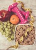 Het concept van de dieetgeschiktheid - domoren, die band, vlokken en verse vruchten op houten lijst meten Stock Foto's