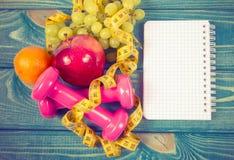 Het concept van de dieetgeschiktheid - domoren, die band, vlokken en verse vruchten op houten lijst meten Royalty-vrije Stock Afbeeldingen