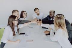 Het concept van de eenheid Close-up van multi etnische mensen die handen houden samen terwijl het rondhangen van het bureau royalty-vrije stock foto's