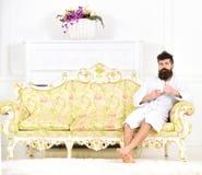Het concept van de elitevrije tijd De mens op slaperig gezicht in badjas, drinkt koffie, in luxehotel in ochtend, witte achtergro stock afbeelding