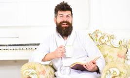 Het concept van de elitevrije tijd De mens slaperig in badjas, drinkt koffie, leest boek in luxehotel in ochtend, witte achtergro royalty-vrije stock afbeelding