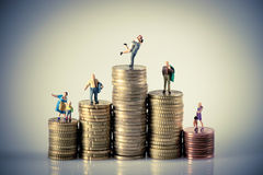 Het concept van de Failybegroting Miniatuurfamilie op muntstukkenstapel Stock Foto