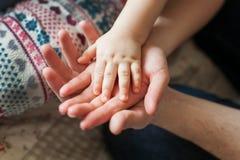 Het concept van de familie Drie handen van de familie - baby, moeder en vader Eenheid, bescherming en geluk Nadruk op zuigelingsh royalty-vrije stock afbeelding