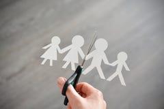 Het concept van de familiescheiding met menselijke document vormen en schaar stock afbeeldingen